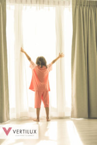 Girl standing at window holding curtains open to look out of large light window at home, instragram look.